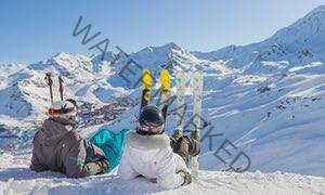Skiers take a break in the snow at Val Thorens, from Montagnes.